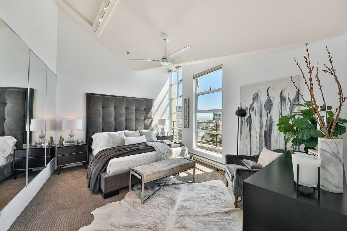 A white room with a high vaulted ceiling, mirrors, a white ceiling fan, and a bed with a high headboard.