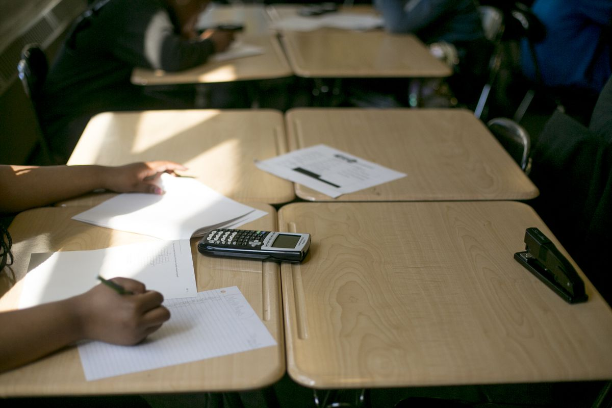 In a close-up of a student's hands in math class, worksheets and a calculator are spread across the desk.