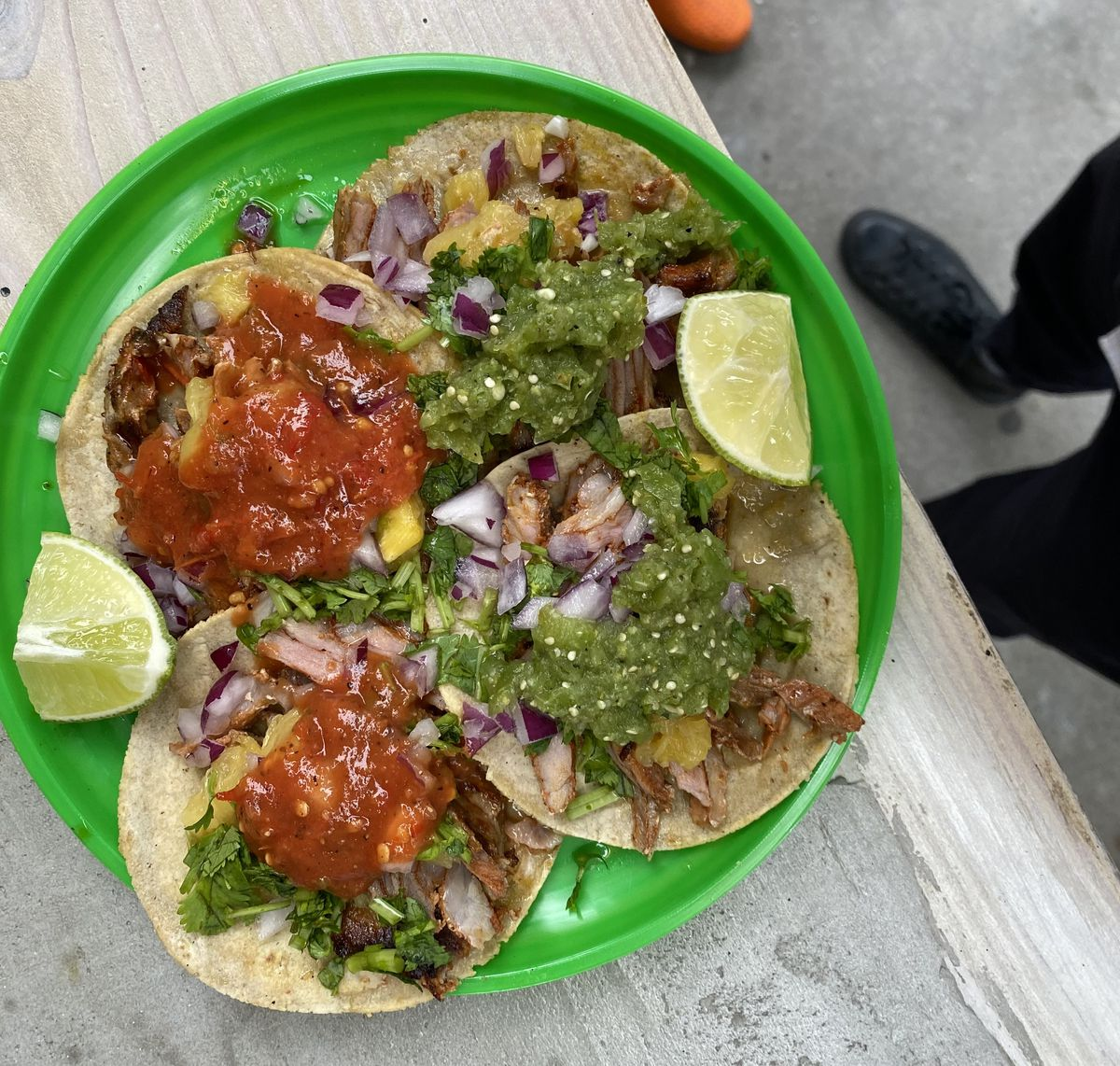 An overhead photograph of four tacos dressed in red and green salsa, cilantro, onion, and lime