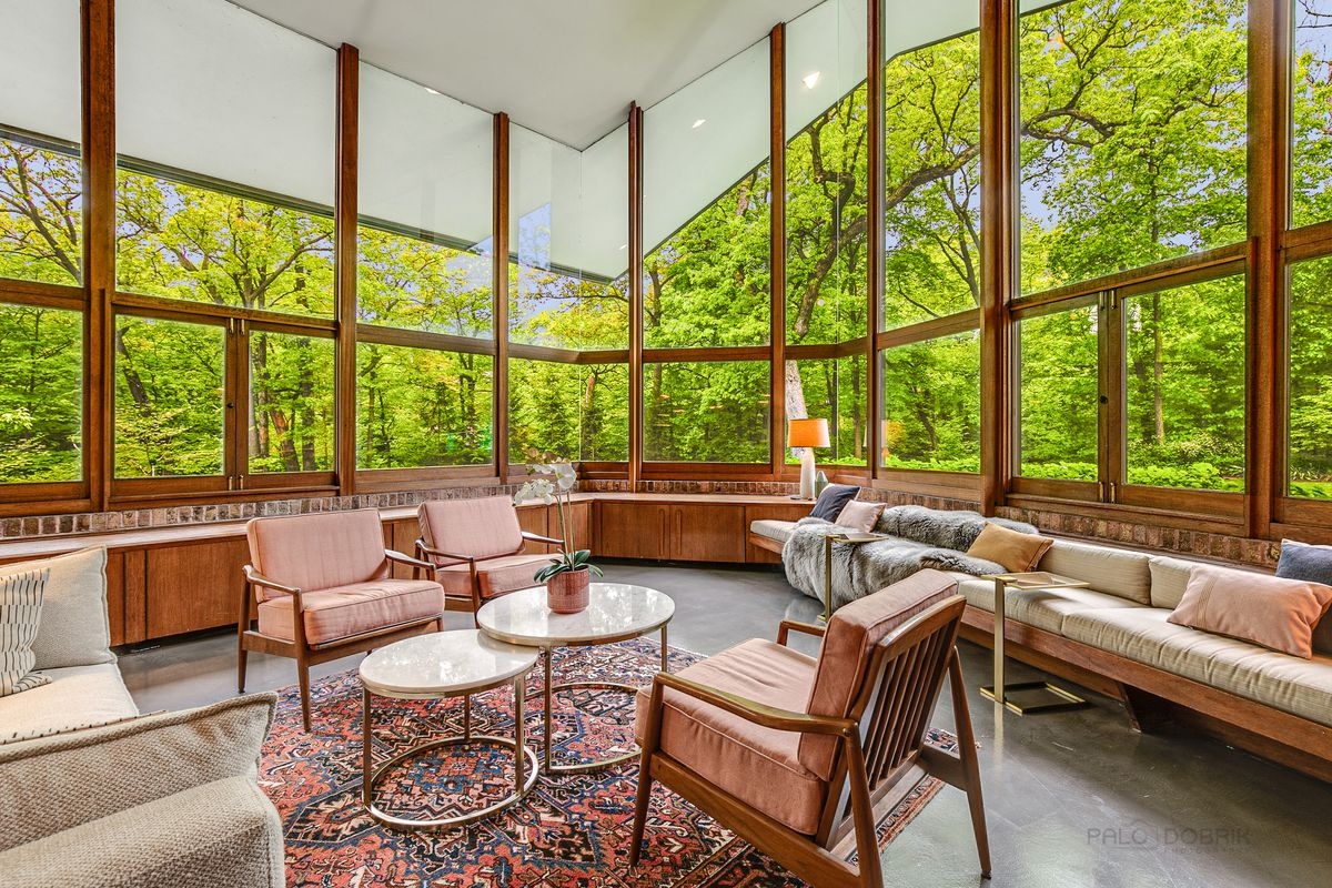 A living room has large windows that look out onto a green backyard.