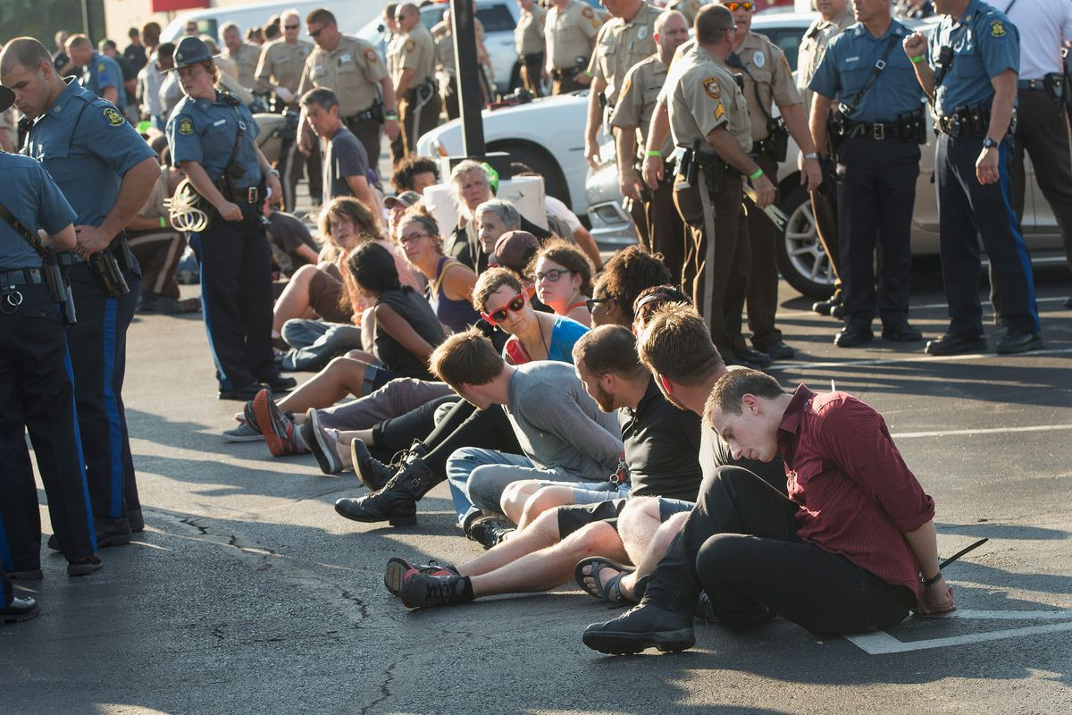 Protesters arrested for blocking a highway in Ferguson, MO on the anniversary of the shooting of Michael Brown.