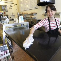 Michelle Miranda cleans a counter while working at The Robin's Nest in Salt Lake City on Tuesday, March 17, 2020. A Salt Lake County health order prohibits dine-in options for all restaurants, taverns, bars, clubs and entertainment venues in an effort to slow the spread of COVID-19.