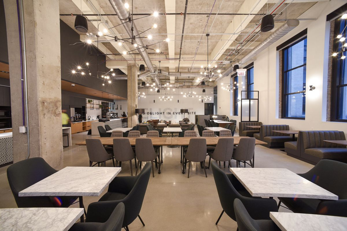 A large work space and cafeteria with exposed concrete columns and globe accent lights.