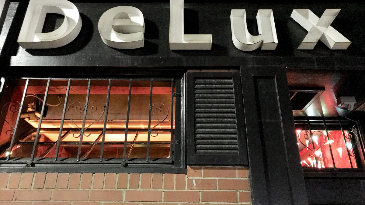 Exterior of a bar with the word DeLux in large white letters on a black background. The exterior wall is brick, and there's a barred window with black shutters on it. A red interior peeks through the front door.