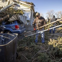 Sean Drake and others help Lyle Bair after high winds blew over two large pine trees at Bair's home in Washington Terrace on Tuesday, Jan. 19, 2021. One of the trees landed on Bair's home, damaging his carport, his car and other items.