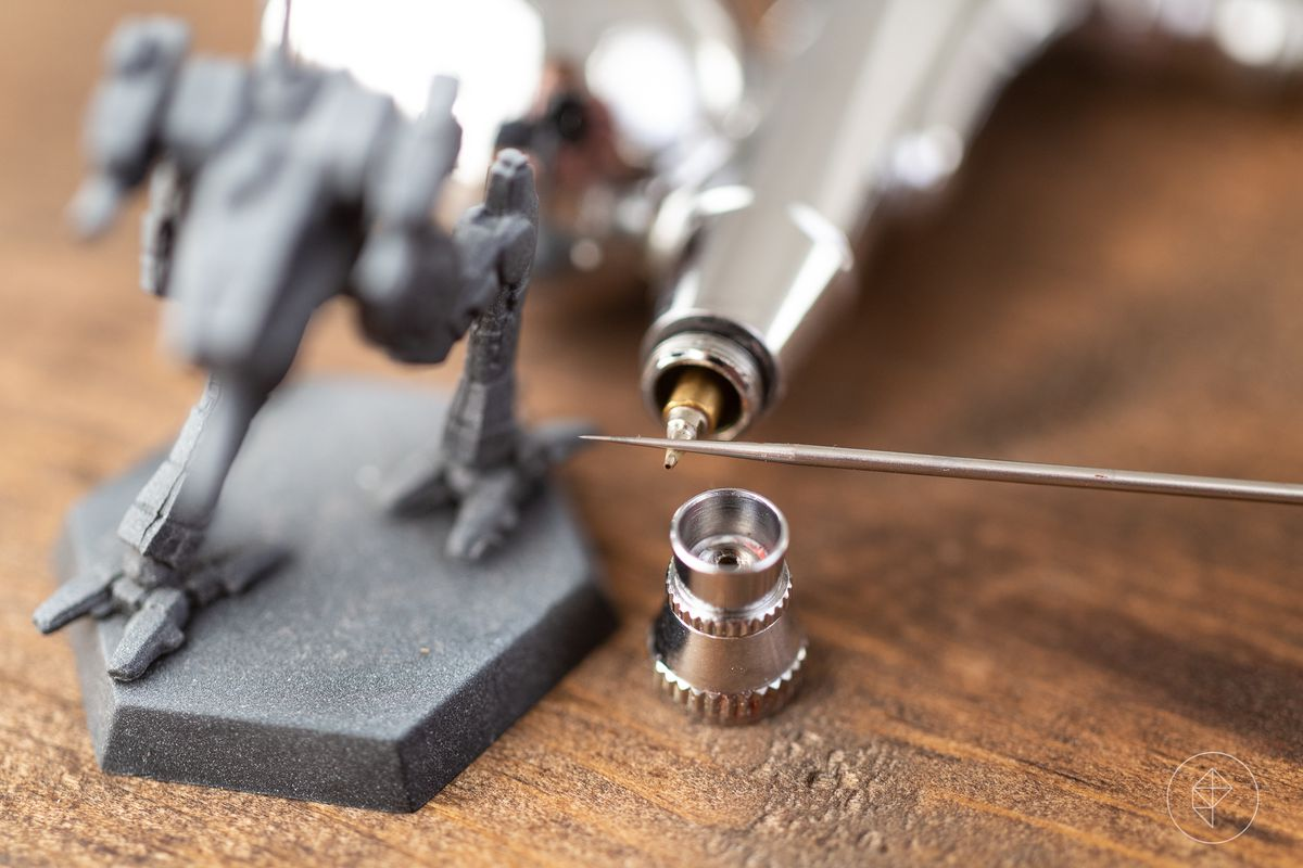 A thin silver needle rests on the business end of an airbrush.