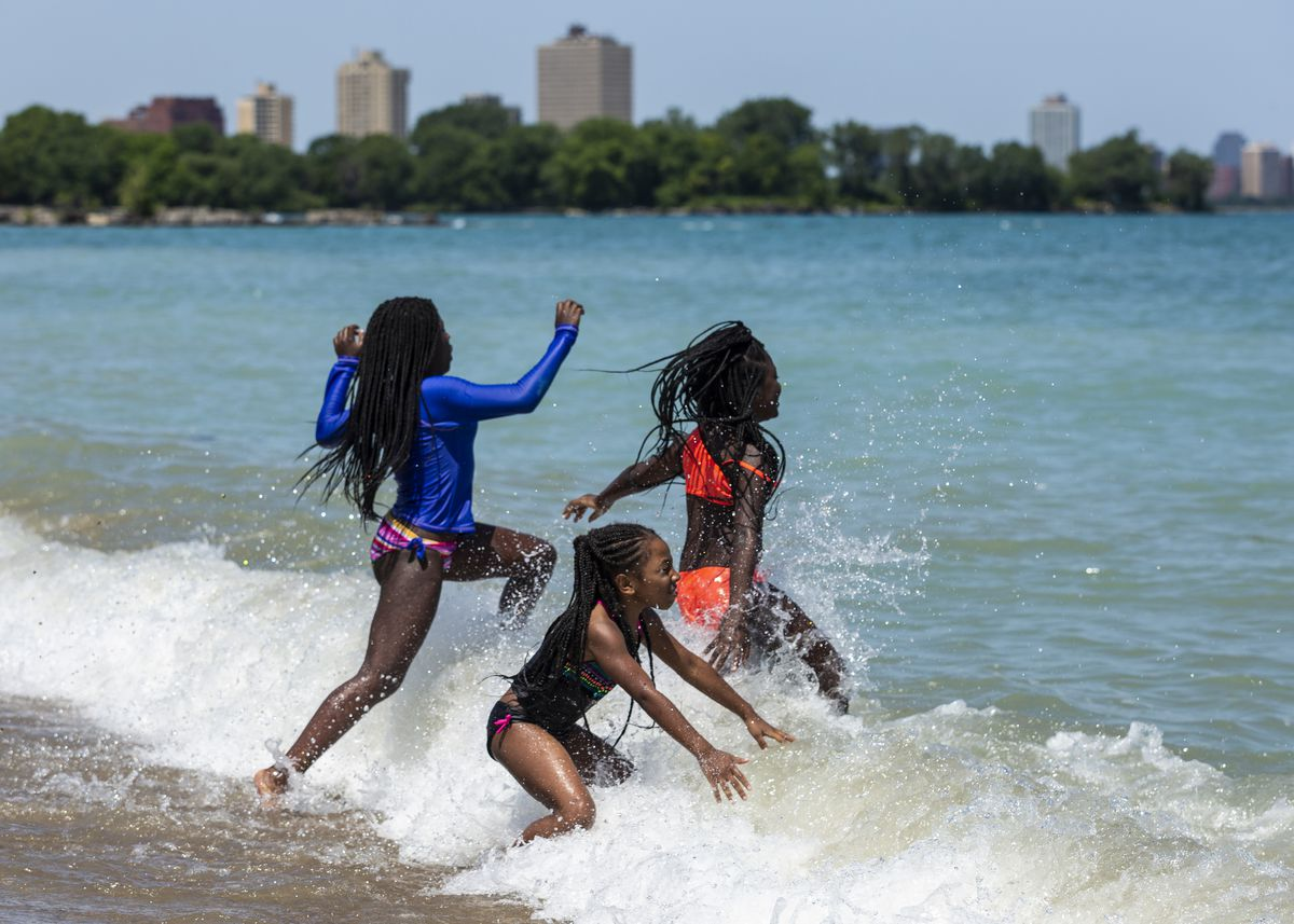 (From left) Cousins Aalihya Barbara, 11, Andrea Martin, 9, and Samarri Mills, 9, all from the South Shore neighborhood, jump in Lake Michigan at Rainbow Beach on the South Side, Wednesday afternoon, July 24, 2019.