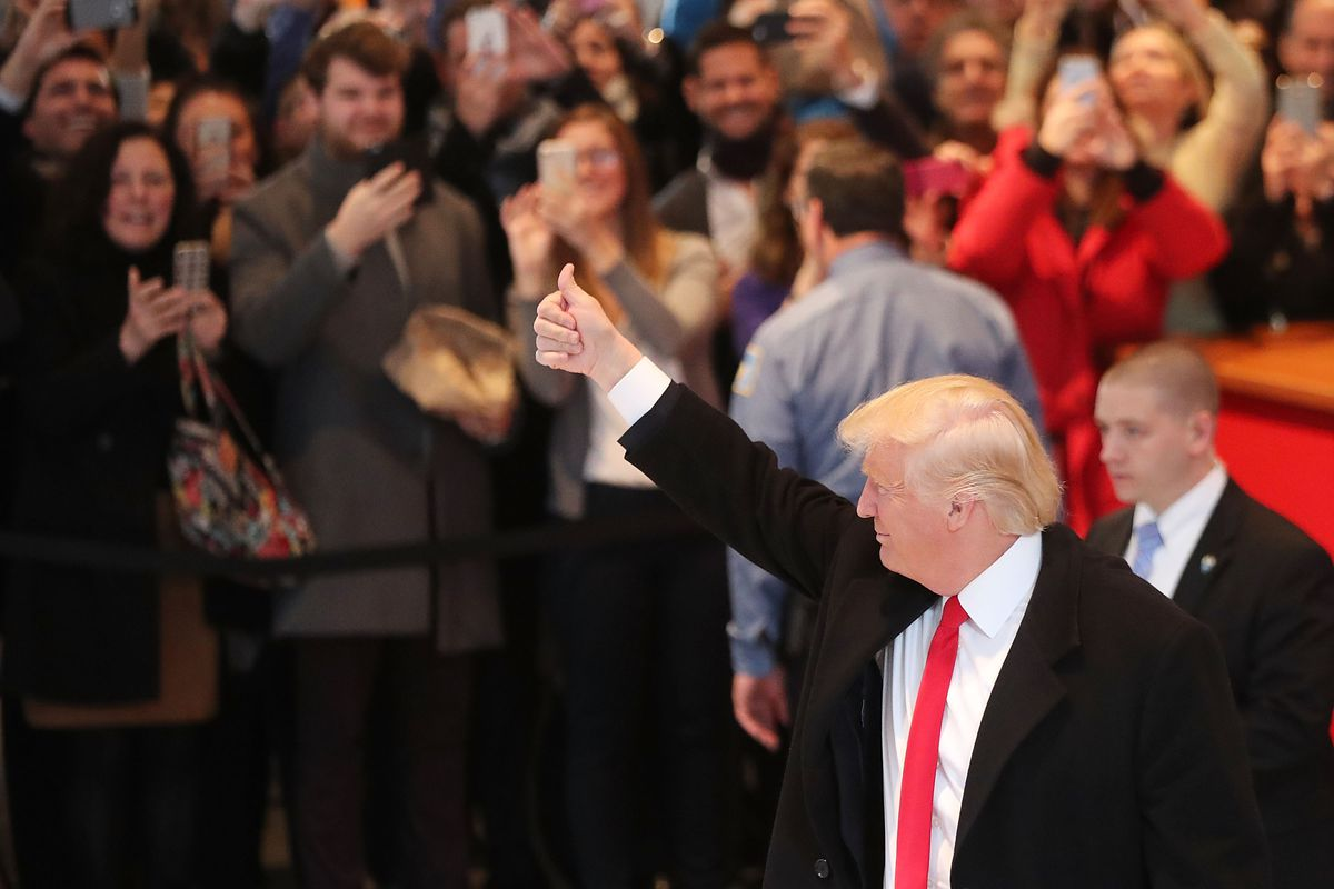 Donald Trump in front of a crowd giving a thumb-up signal.