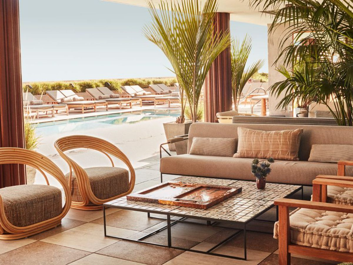 A mod, plush rooftop lounge area with throwback seating near a pool at summertime.
