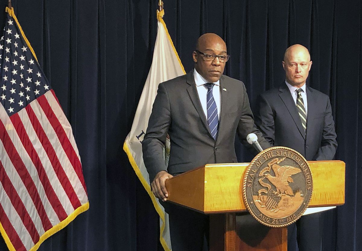 Attorney General Kwame Raoul, left, speaks at a news conference in 2019.