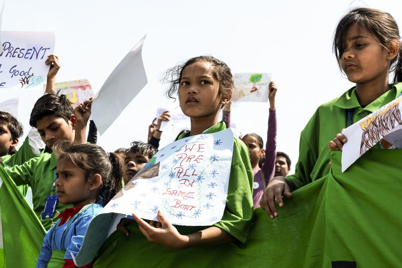 An Indian child carries a placard as she participates in a school strike called 'Fridays for future' to protest against climate change in New Delhi, India, on March 15, 2019.