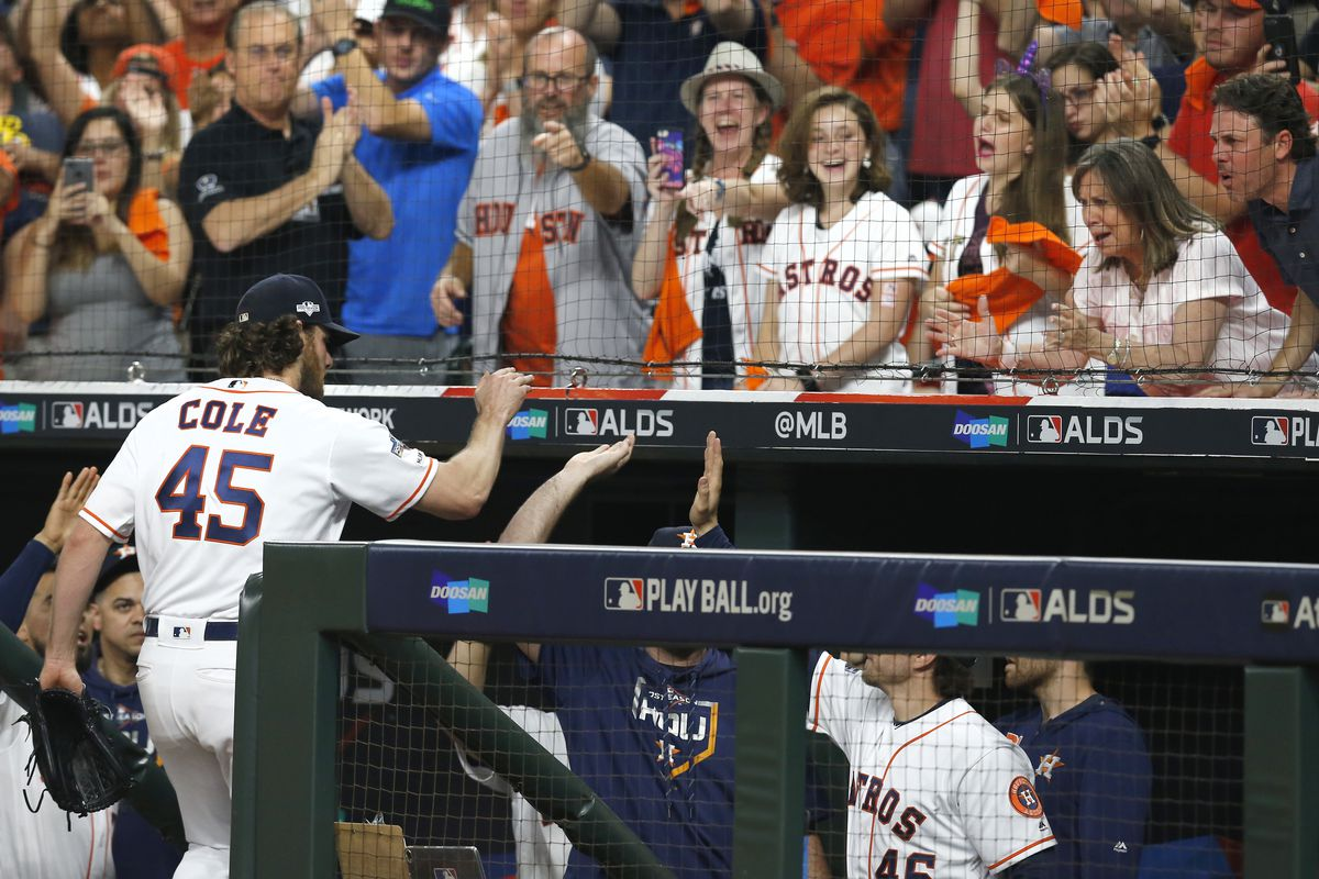 Starting pitcher Gerrit Cole of the Houston Astros high fives his teammates as the crowd cheers after he leaves the game in the eighth inning of Game 2 of the ALDS against the Tampa Bay Rays at Minute Maid Park on October 05, 2019 in Houston, Texas.