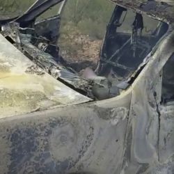 This frame from Nov. 4, 2019, video by Kenny Miller and posted on the Twitter account of Alex LeBaron shows a burned-out vehicle that was being used by some members of the LeBaron family as they were driving in a convoy near the Sonora-Chihuahua border in Mexico. Mexican authorities say drug cartel gunmen ambushed multiple vehicles, including this one, slaughtering several women and children.