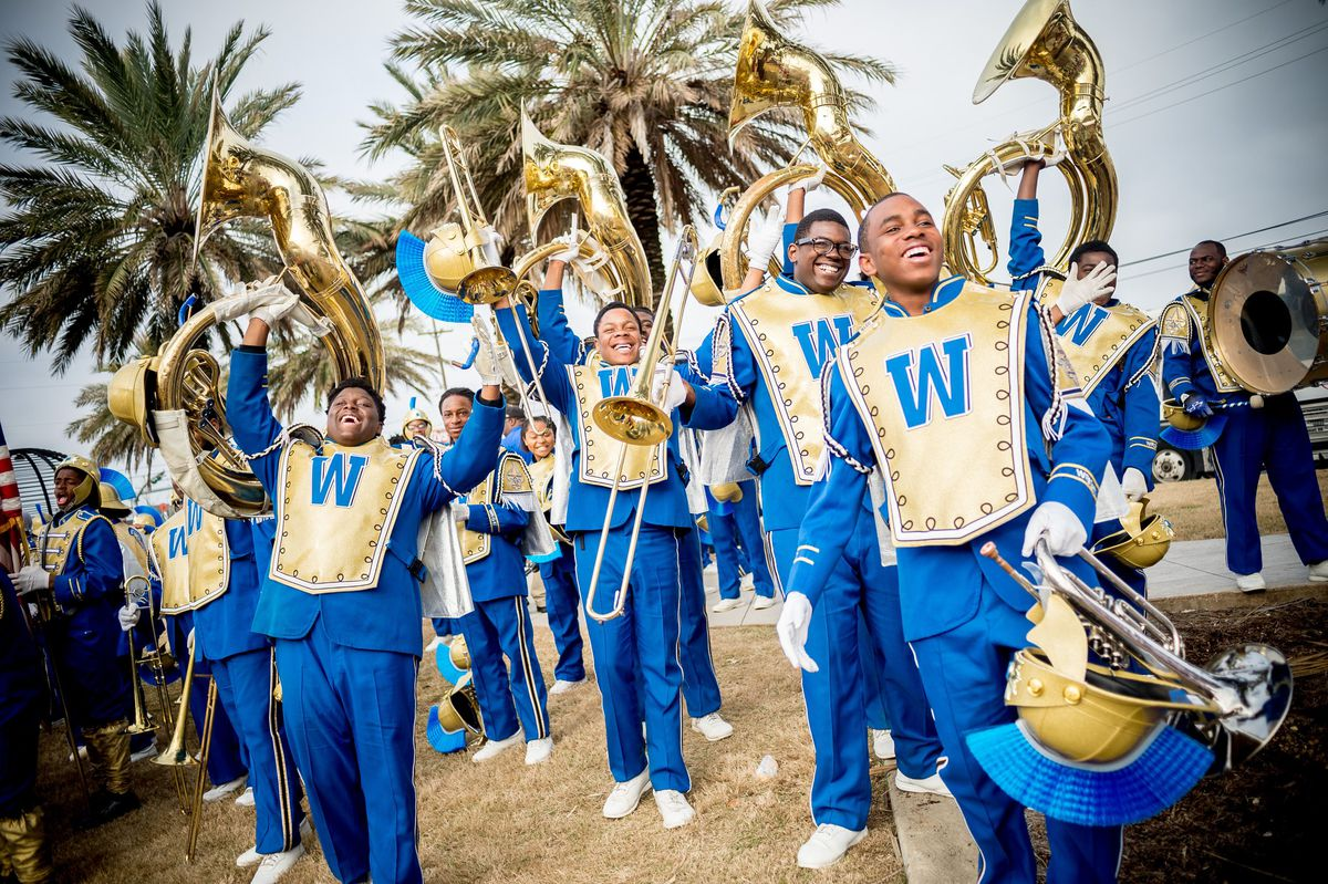 Members of a marching band hoist their tubas in front of a backdrop of palm trees