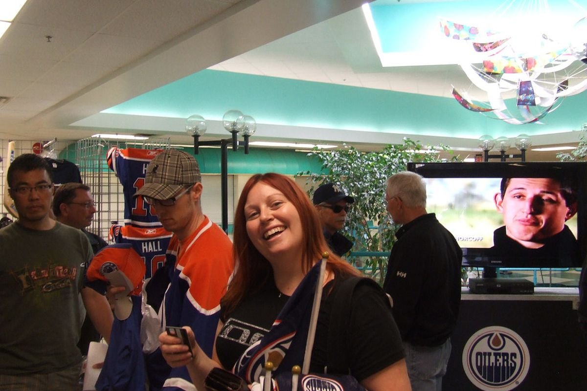 Armed and dangerous: The irrepressible BlueBelle visits the merch table at Oilers summer development camp.  (Photo: Bruce McCurdy)