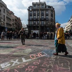 A man walks by solidarity messages written in chalk outside the stock exchange in Brussels on Tuesday, March 22, 2016. Explosions, at least one likely caused by a suicide bomber, rocked the Brussels airport and subway system Tuesday, prompting a lockdown of the Belgian capital and heightened security across Europe. At least 26 people were reported dead.