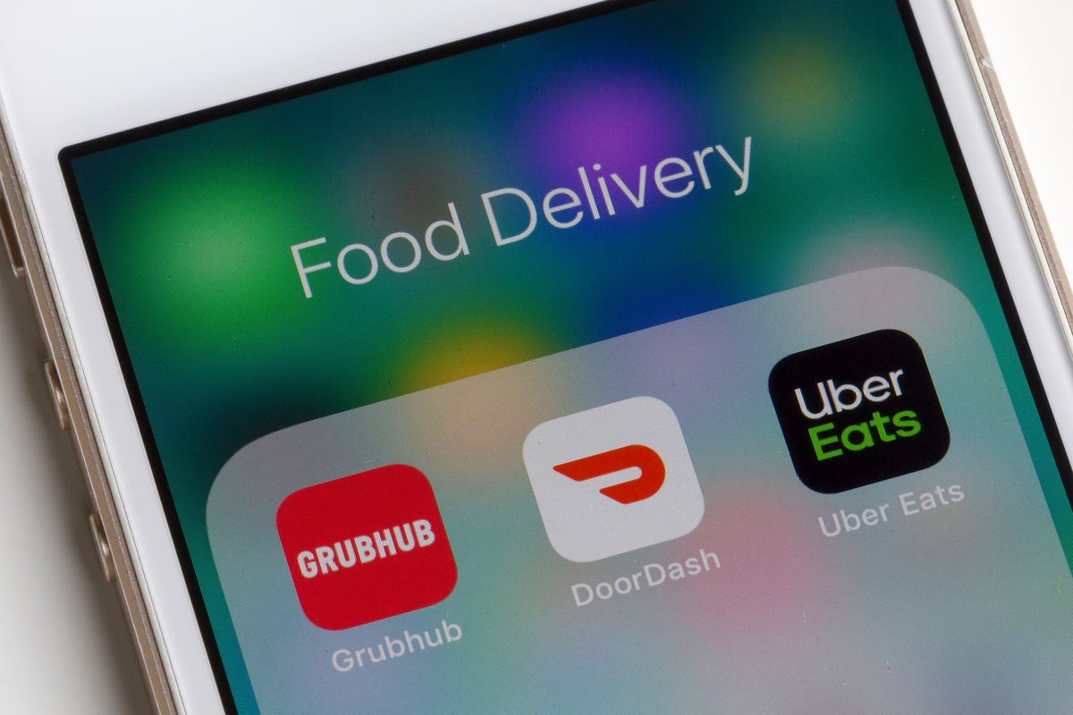 """An iPhone displays the icons of Grubhub, Doordash, and Uber Eats under the """"food delivery"""" category."""