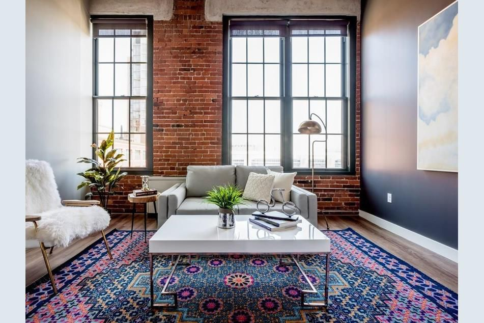 A living room with a brick wall and high ceilings as well as furniture.