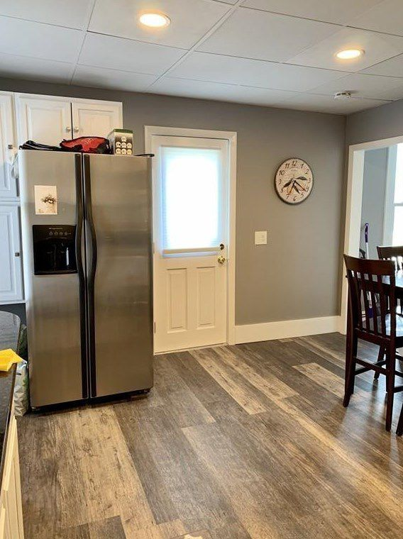 Part of a kitchen with a fridge and a door visible.