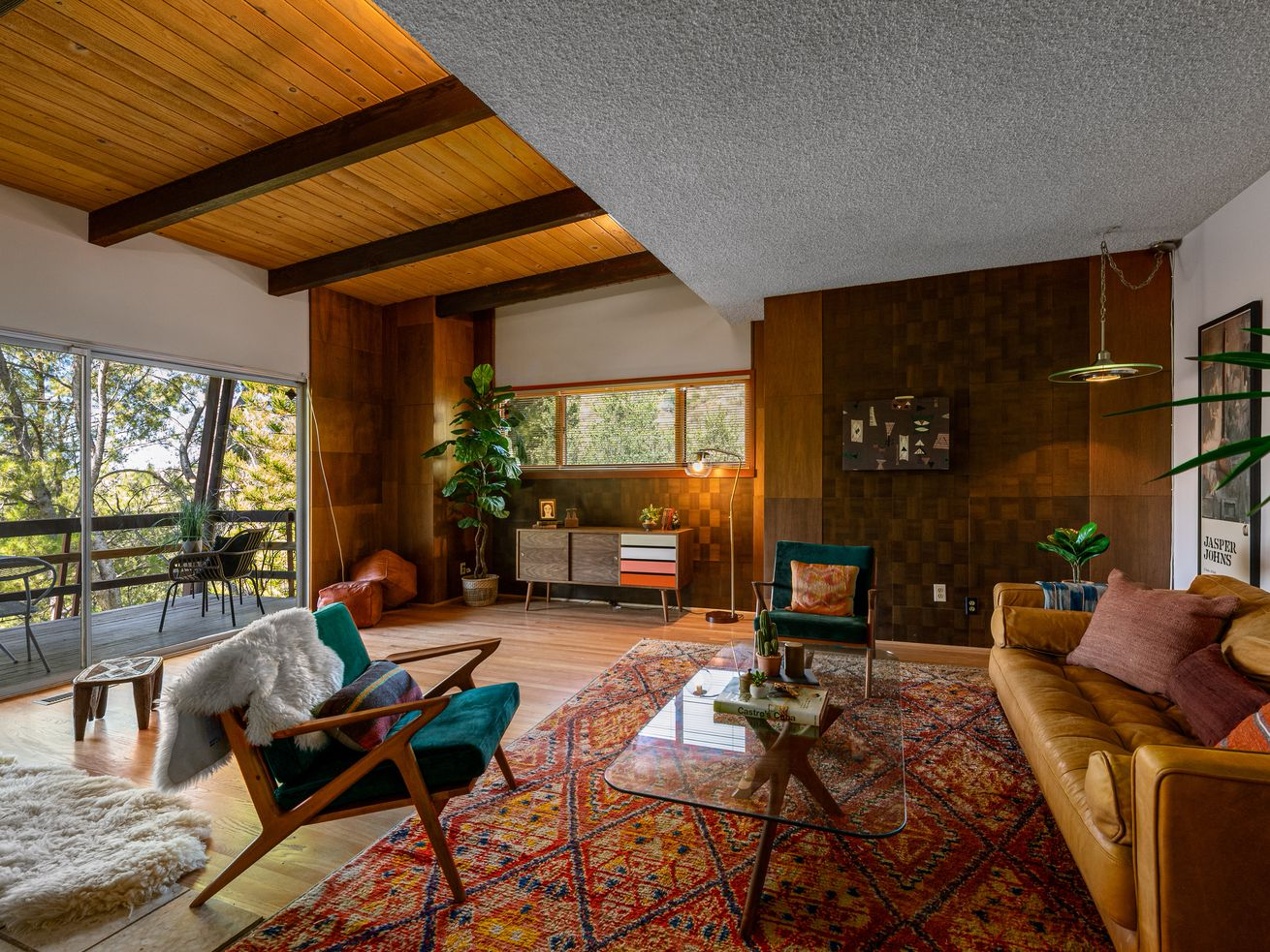 Living room with sliding glass doors and wood-paneled walls.