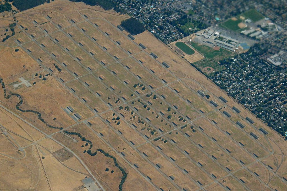 An aerial photo of the Concord Navy base, with gray concrete structures dotting a plain of yellow grass.
