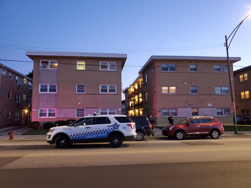 Chicago police vehicles sit outside a condo complex Saturday in the 6700 block of West Irving Park Road.