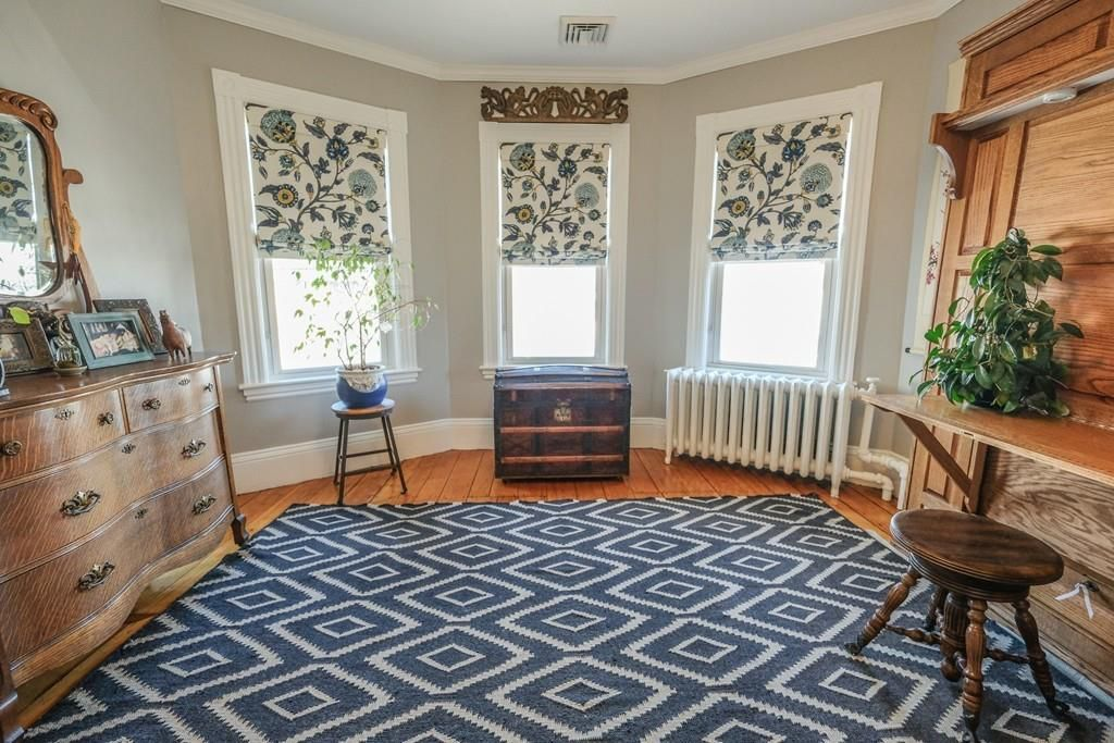 A room with a bay window and a striking rug with diamond shapes on it.