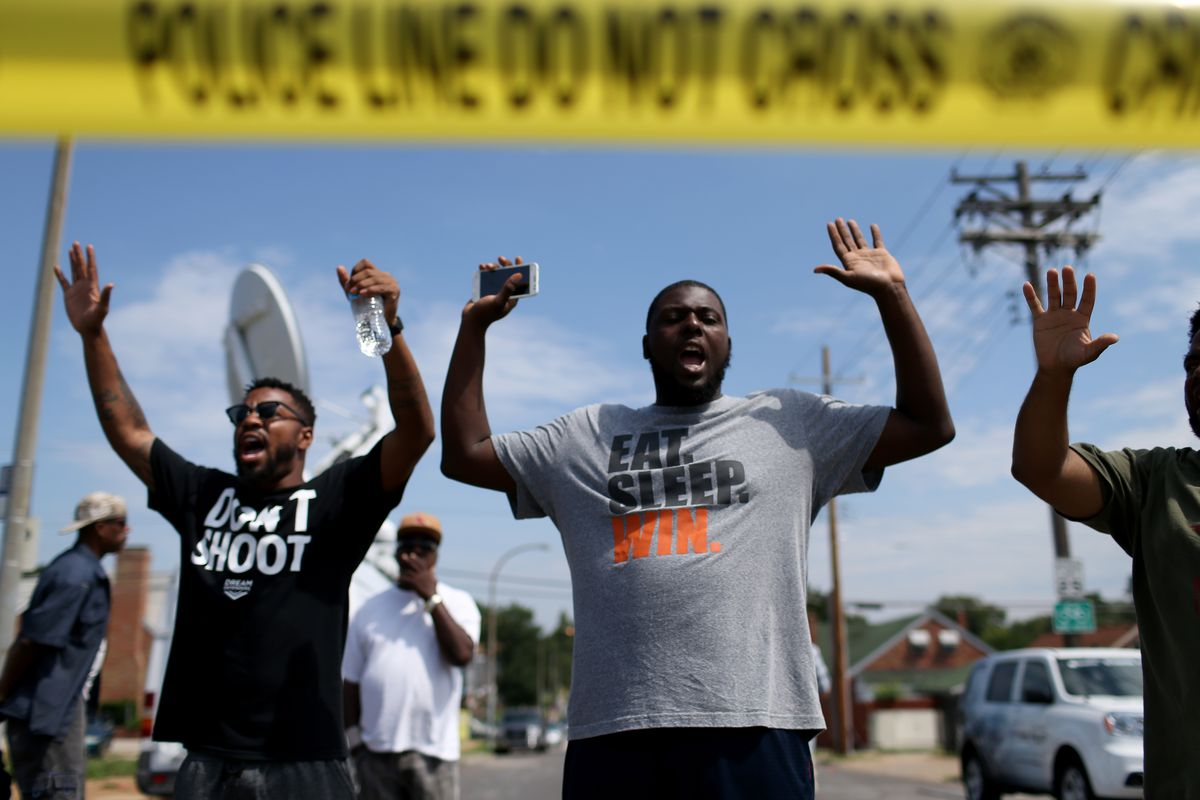 Protesters in St. Louis, Missouri, hold their hands up in support of Michael Brown.