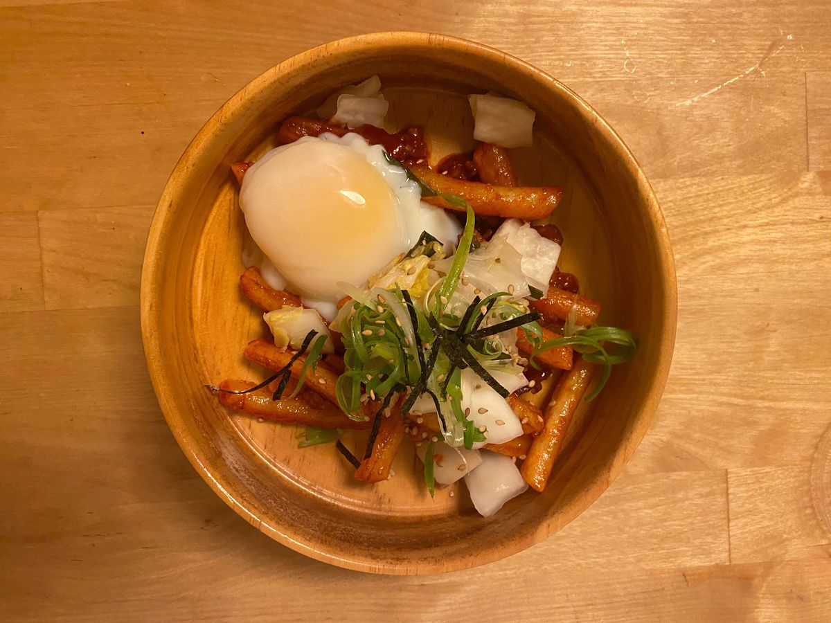 A bowl of tteokboki with a poached egg, scallions, and kimchi sitting on a wooden table