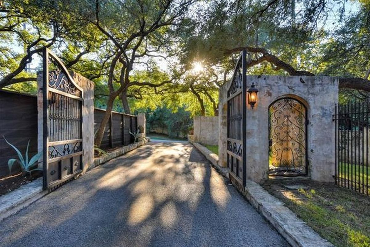 Elaborate but dated 1970s gated entry with wrought-orn fence and concrete archways, big trees