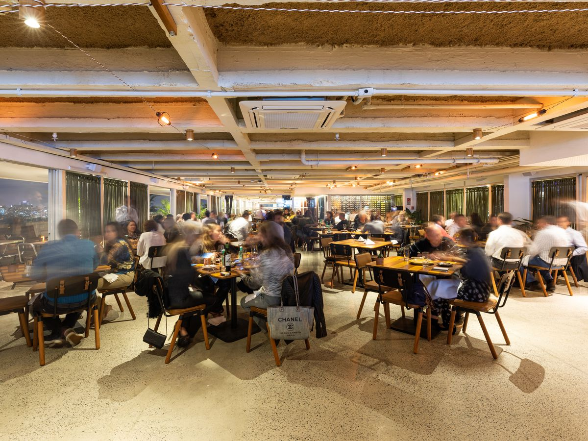 A bustling dining room with exposed ceiling beams and glowing orange lighting, with diners seated at simple wooden tables and others blurred as they walk around