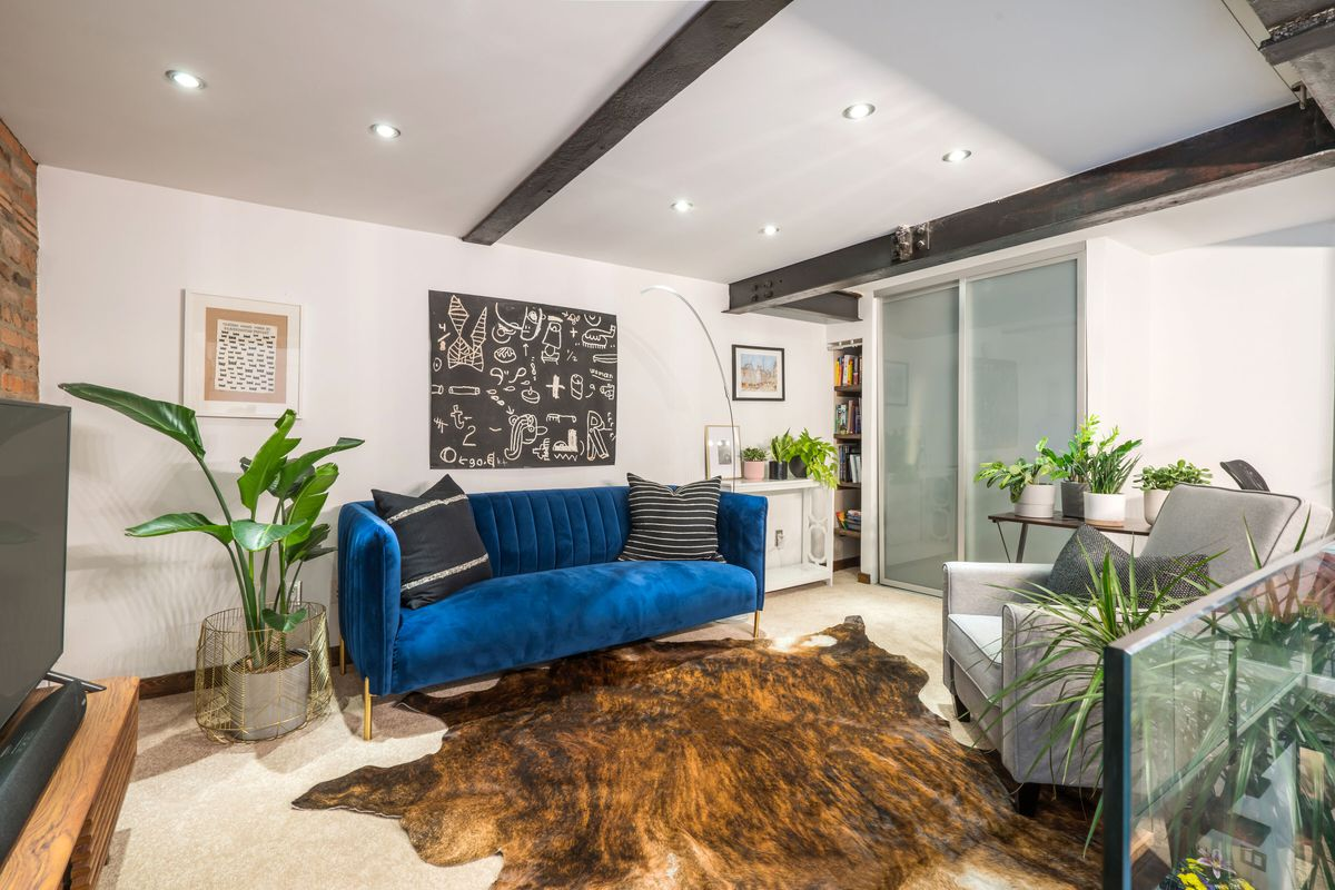 A living area with a bright blue couch, white walls, several planters, and cast iron beams.