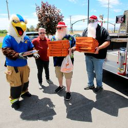 Mascot Dr. Inferno, Travis Normin (aka Santa Travis) and Steve Egginton prepare to make a presentation to firefighters Fire Station No. 51 in Layton on Friday, May 15, 2020. Organizers of the Sounds of Freedom Festivalorganizers delivered Little Caesars pizza to first responders in Davis County while driving in a restored 1939 firetruck that was used at Kennecott Copper in the '40s and restored for Shriner's Hospital for Children.