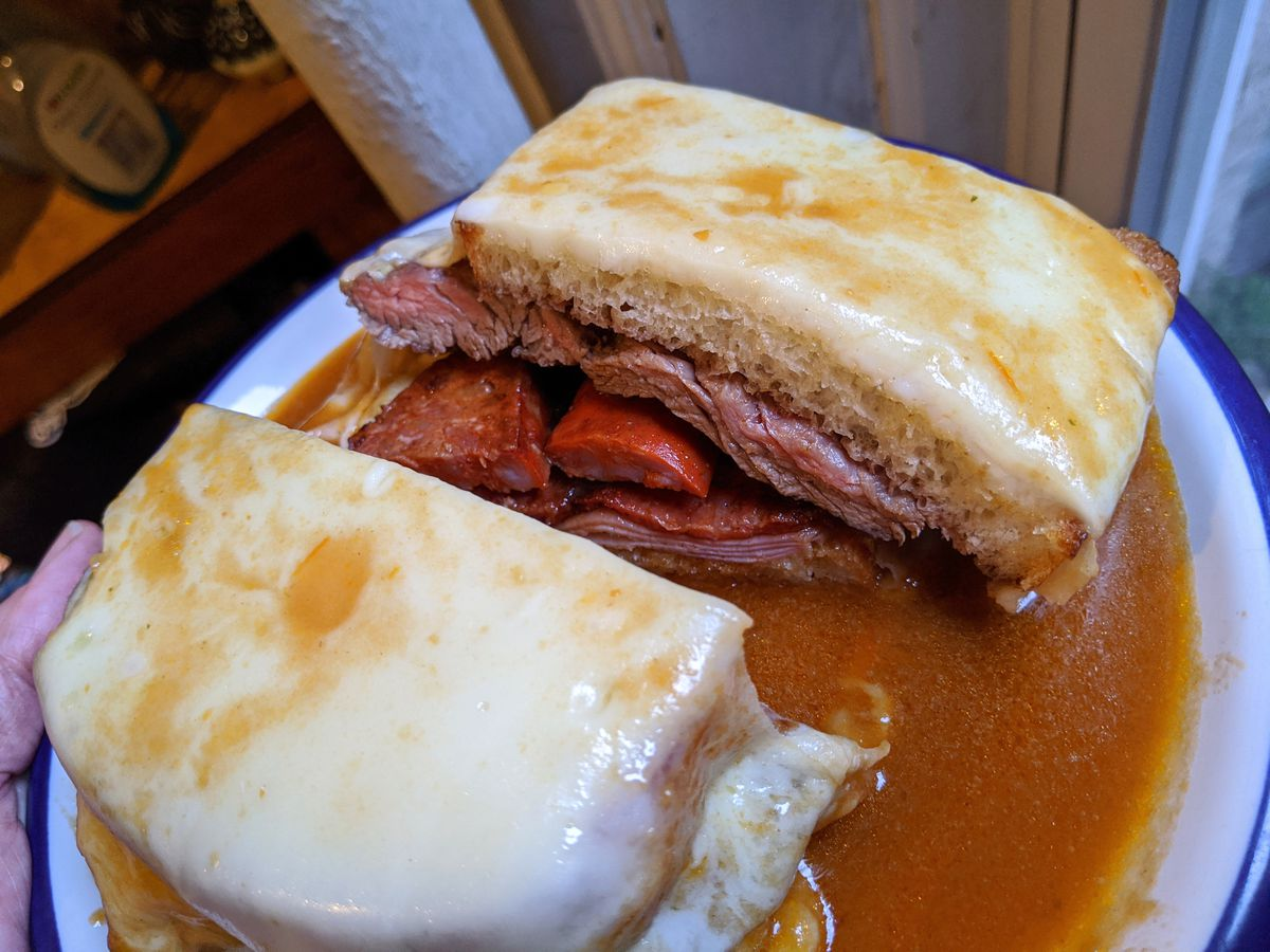 A square sandwich mantled in gooey cheese with meats spilling out in the center of the cut halves and pink gravy underneath.