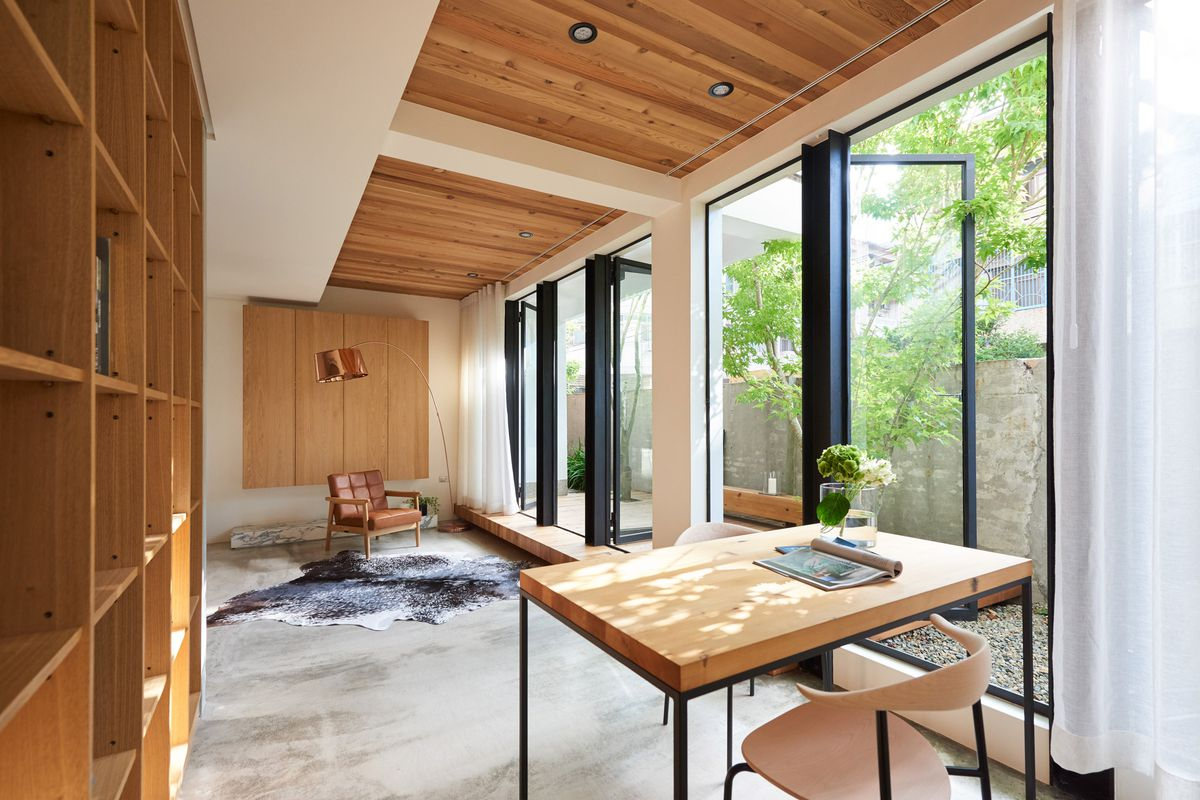 Interior shot of first floor living room with wall of glass doors opening onto a patio planted with trees. The floor is concrete, with wood paneling on the ceiling, white walls, and a wall of built-in shelving. Sparsely furnished.
