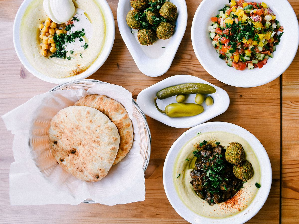 Hummus, pita, and pickles on a wooden table.