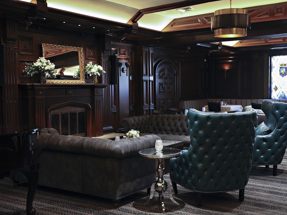 Two large teal chairs sit in a lounge, before a fireplace