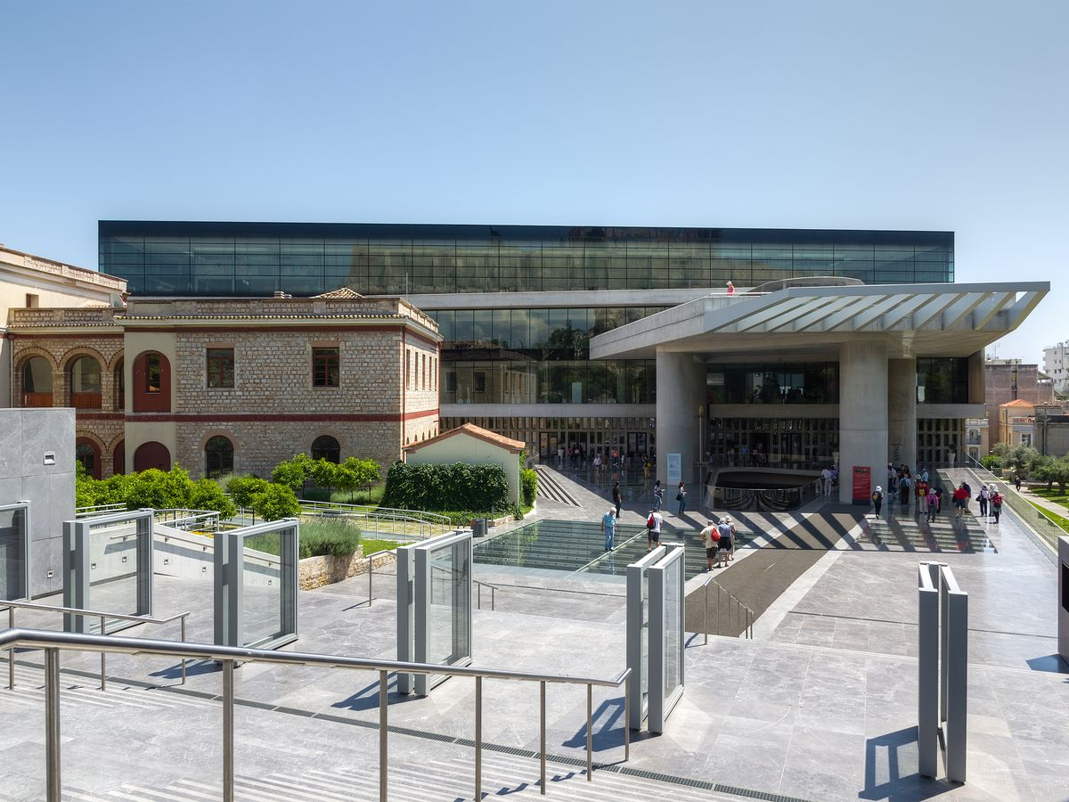 The exterior of the Acropolis Museum in Athens. The facade is partially glass.