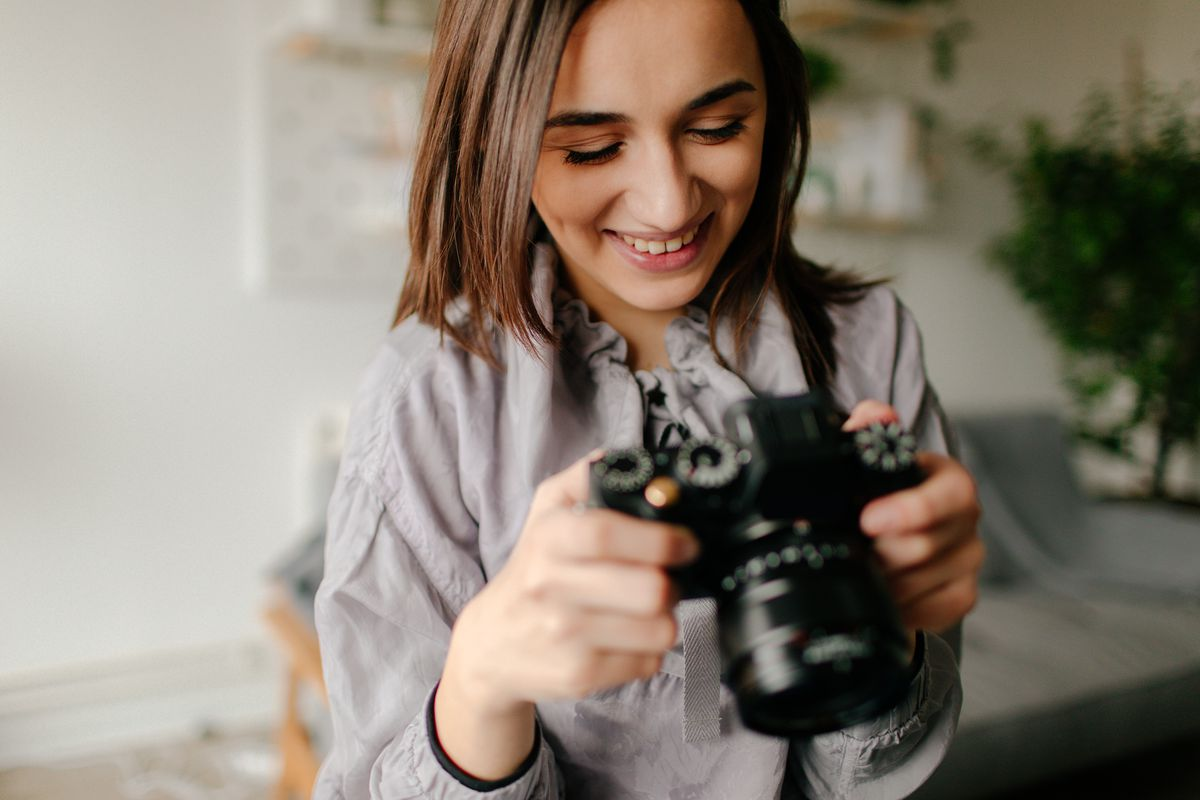 A woman looks at the back of her camera.