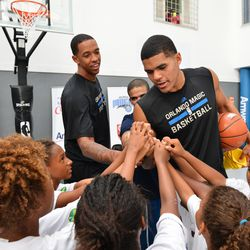 Magic players Tobias Harris and Channing Frye assist with a basketball clinic in Rio for local youth.