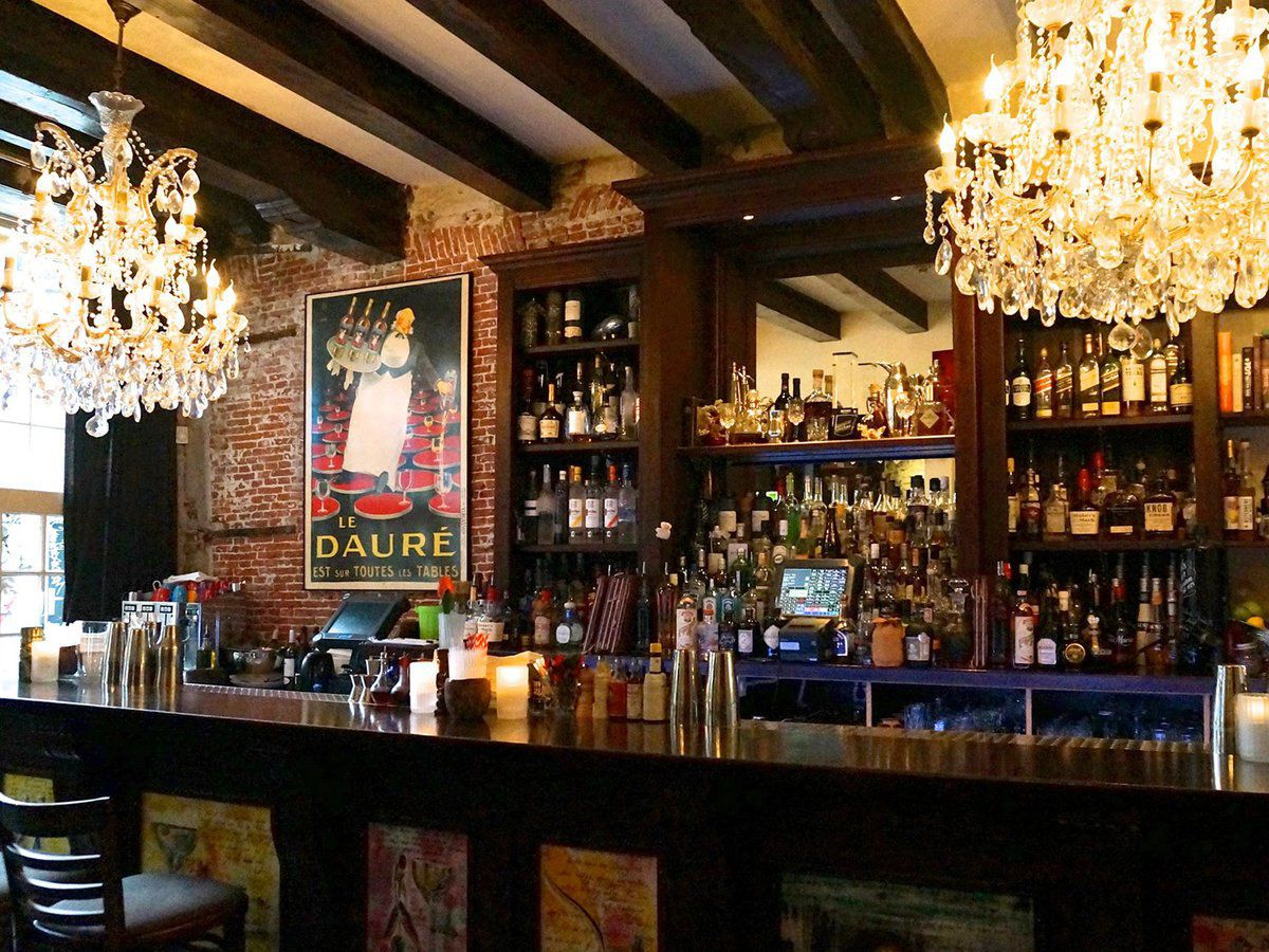 A bar lit by natural light and large ornate chandeliers hanging low overhead, with an exposed brick wall in the back, bottles lining bar shelves, and a poster of a vintage liquor advertisement.