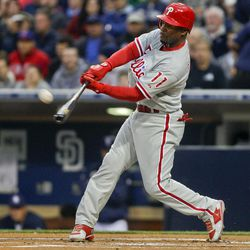 Philadelphia Phillies' Jimmy Rollins lofts a sacrifice fly to right field to drive in Juan Pierre from third base in the first inning of a baseball game against the San Diego Padres Thursday, April 19, 2012, in San Diego.