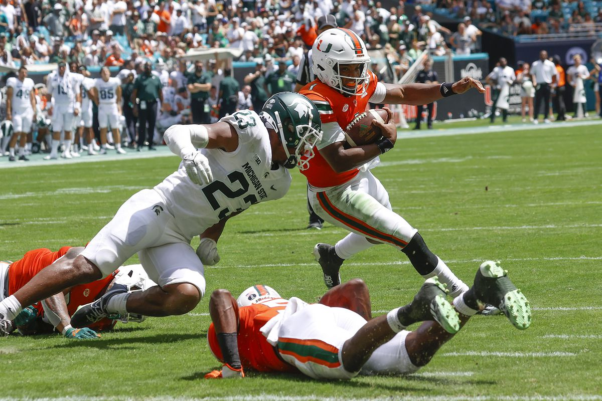 D'Eriq King of the Miami Hurricanes is pursued by Darius Snow of the Michigan State Spartans as he scrambles out of the pocket on September 18, 2021 at Hard Rock Stadium in Miami Gardens, Florida. .