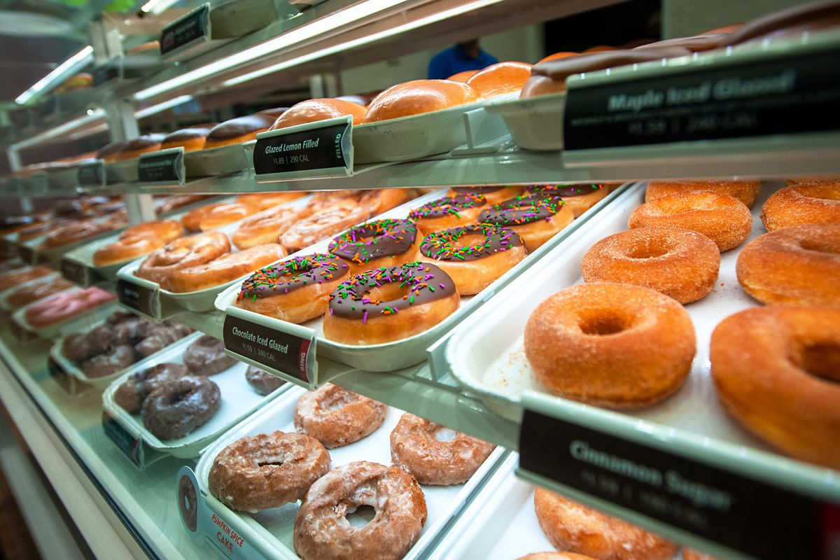 A glass pastry case filled with Krispy Kreme doughnuts.