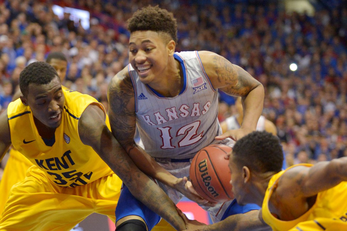 Kelly Oubre Jr. smiles while preparing to put up a shot over two Kent defenders.