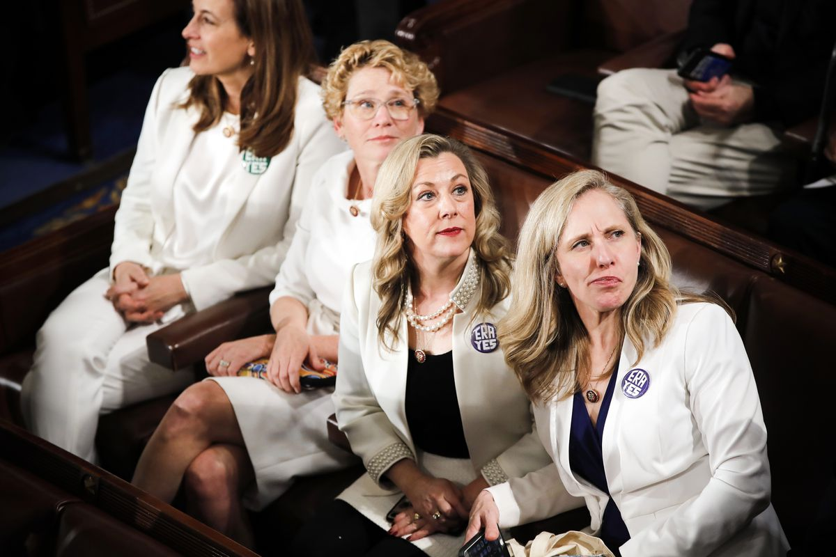 """Democratic congresswomen wearing white suits with green buttons reading """"ERA Yes."""""""