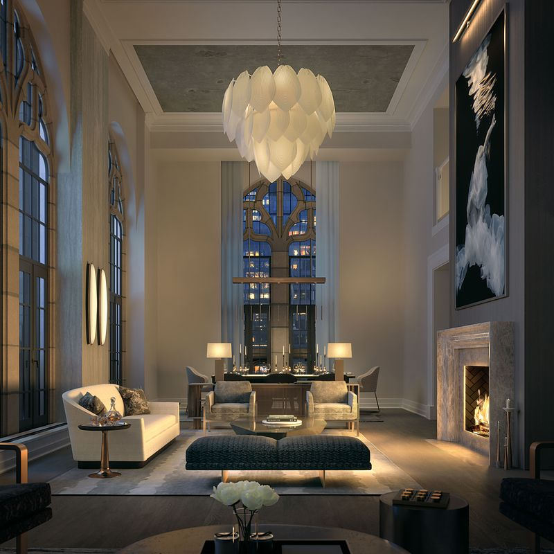 A soaring ceiling with a coffered style and a flower-like white chanelier hanging over a living room with a bench, white couch, and two chairs facing a roaring marble fireplace with elegant black and white art hanging above.