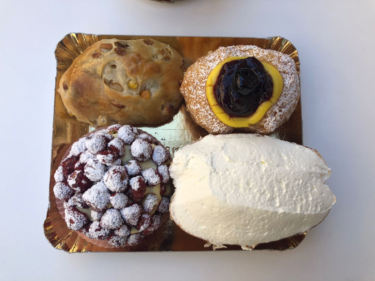 Maritozzo, shown here on the bottom right from a bakery in Roman, are sweet yeasty rolls brimming with whipped cream.