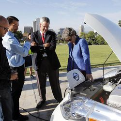 Rep. Patrice Arent, D-Millcreek, right, Rep. Edward Redd, R-Logan, Jared Campbell and John Loveless look at Loveless' electric vehicle following a press briefing concerning alternative fuel vehicle strategies at the Capitol in Salt Lake City, Wednesday, Aug. 7, 2013.