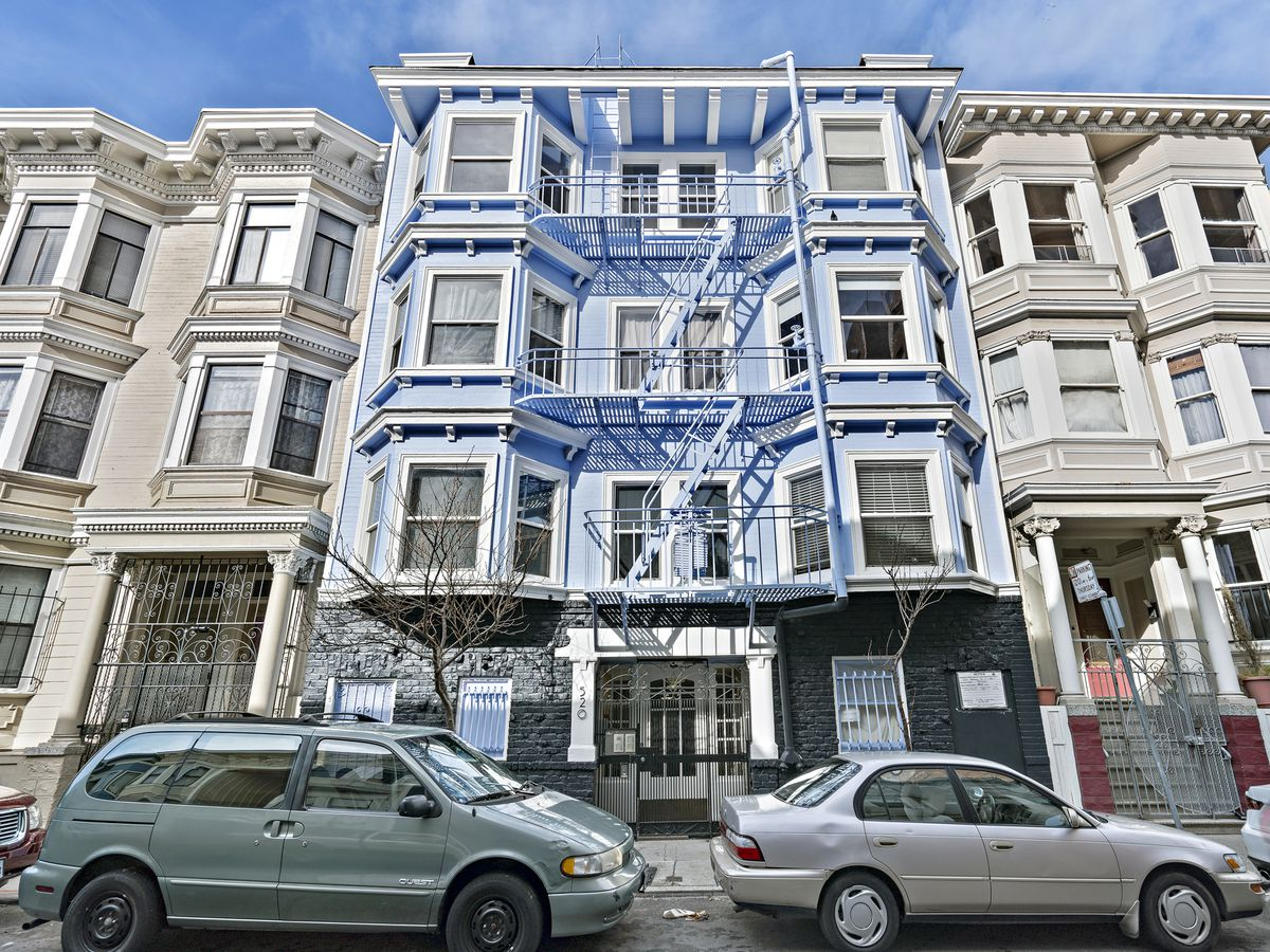A four-story building painted blue with bay windows.